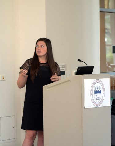 A female student stands a podium and looks up at a screen during her presentation.
