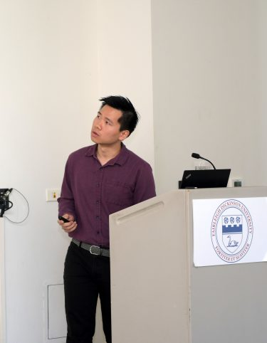 A male student stands at a podium and looks up at a screen while presenting his research.