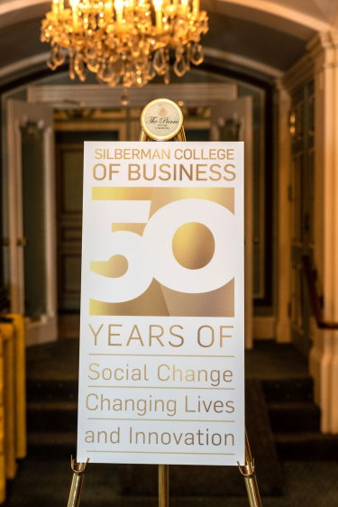 """A sign reads """"Silberman College of Business 50 years of social change, changing lives and innovation."""