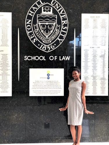 A woman poses in front of a wall that reads Seton Hall University School of Law.