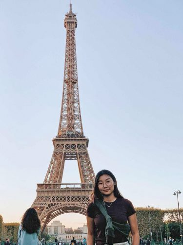 A woman stands near the Eiffel Tower.
