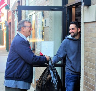 A man hands a garbage bag to another man.