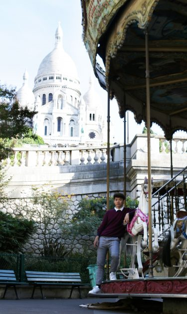 Viet stands in front of a church and carousel.