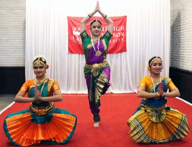 Three female Bollywood dancers strike a dance pose.