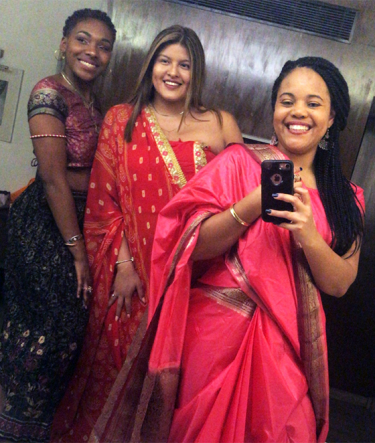 The female students take a photo of themselves wearing saris.