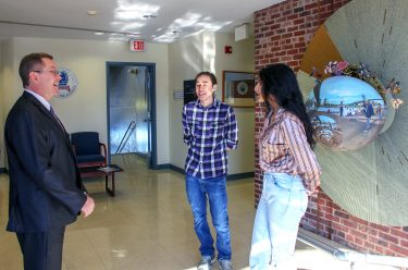 Nelson talks with two students.