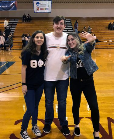 Three students pose for a photo inside of a gymnasium.
