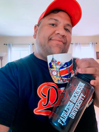 A young man holds up a British-themed coffee mug and an FDU water bottle.