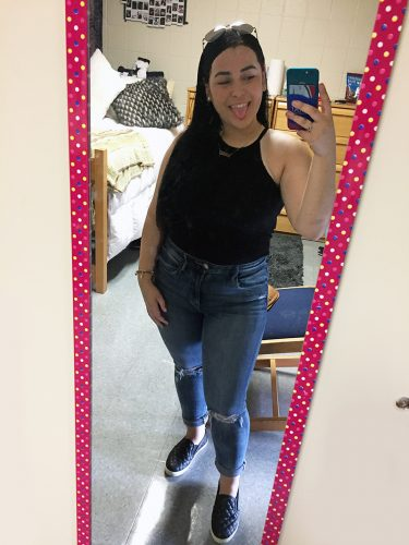 A young woman takes a mirror selfie.