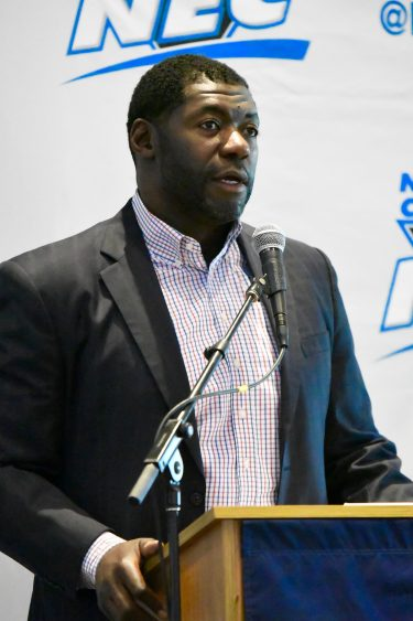 "Roman Oben stands a podium with a backdrop that reads ""NEC"" behind him."